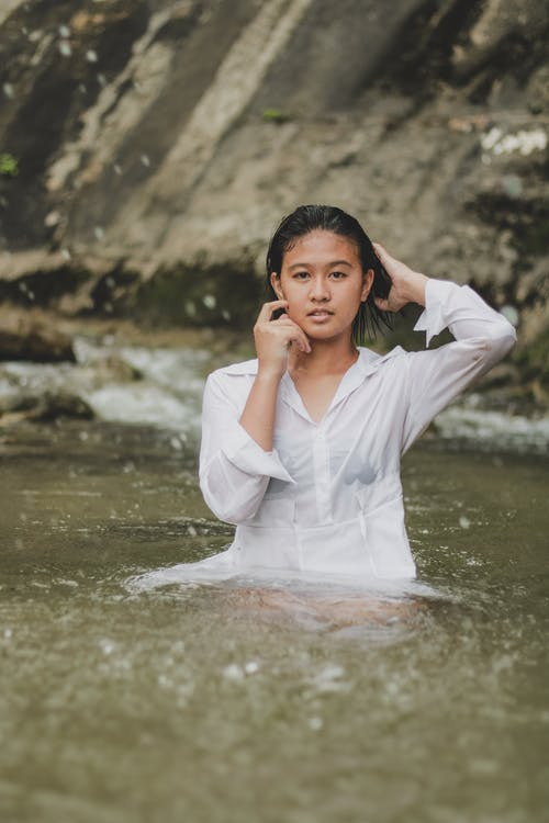 Attractive young Asian female in wet white shirt touching head gently and looking at camera while standing in peaceful lake in nature