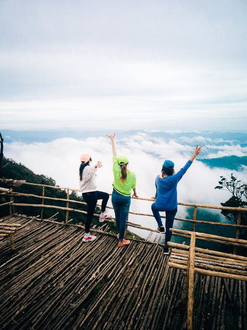 Unrecognizable women standing on viewpoint against cloudy sky