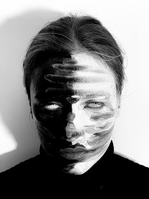 Black and white of scary young female with creative makeup and blank eyes standing in studio and looking at camera