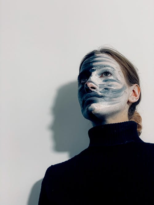 From below of unemotional young female model with painted face in black turtleneck standing against white background and looking away