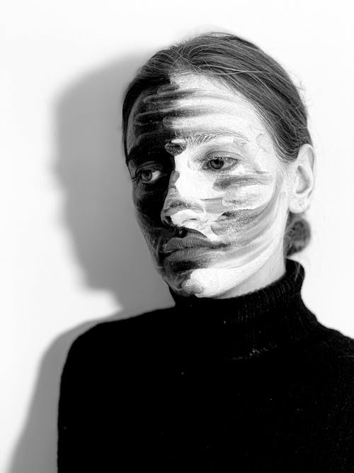 Melancholic young female model with black and white paints on face