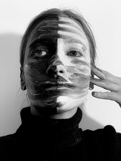 Black and whit of calm young lady applying contrast paints on face and looking away