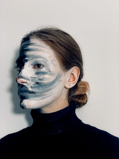 Extraordinary female with body art on face looking away on white background in studio