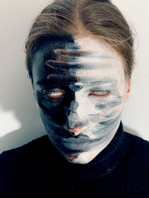 Young spooky female with blue lips and body art on face on white background