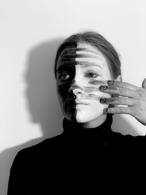 Black and white of emotionless female with body art on face looking away on white background