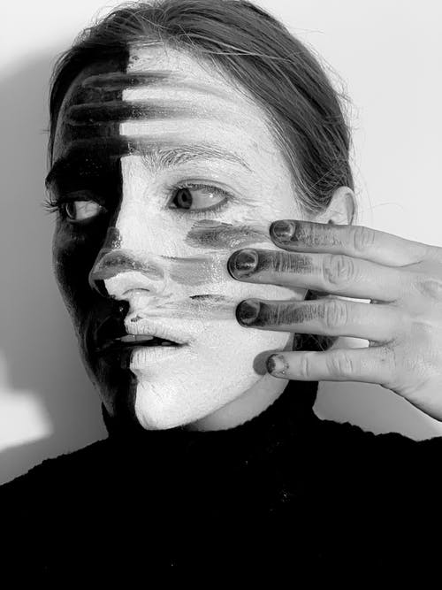 Strange woman with paint on face and hand