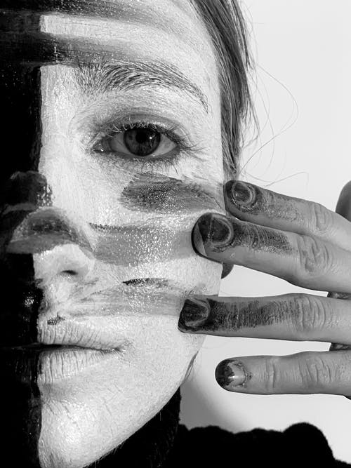 Black and white of crop young female with body art on face on white background