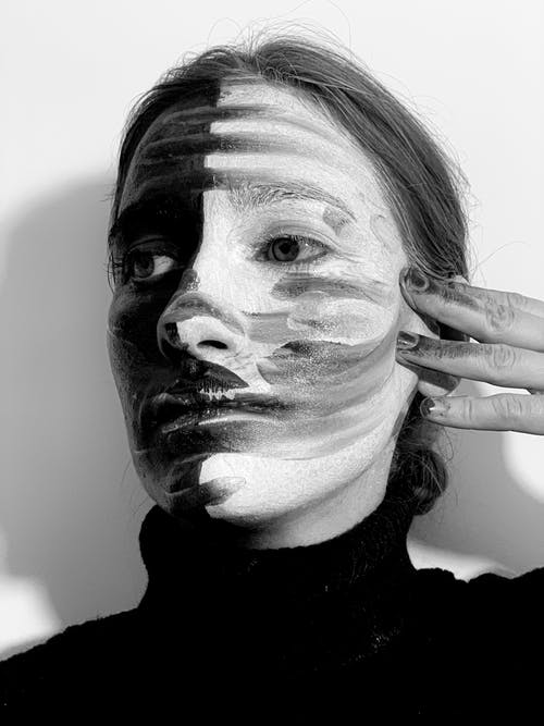 From below black and white of weird disappointed female smearing greasepaint on face with messy hand while looking away on white background