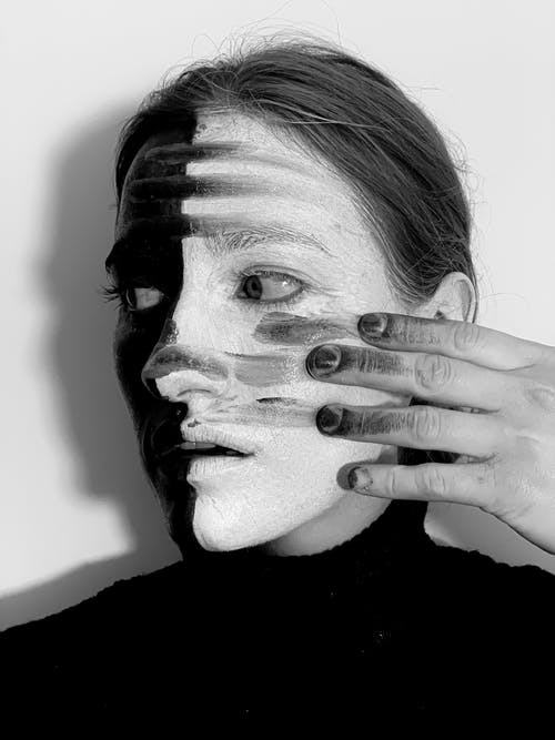 Spooky woman with smeared paints on face