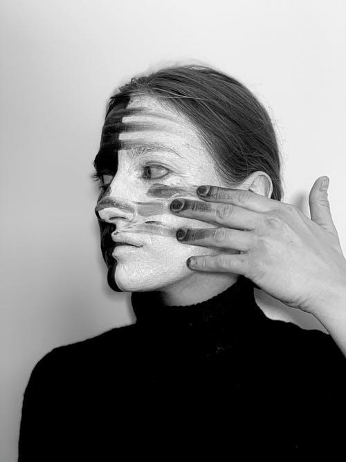 Black and white side view of watchful female smearing greasepaint on face with dirty hand and looking into distance on white background