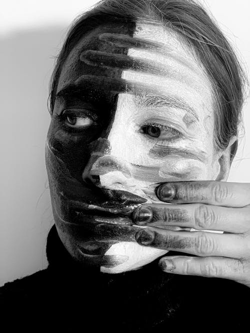Black and white headshot of strange female smearing paints on face with dirty hand and looking away while standing on white background