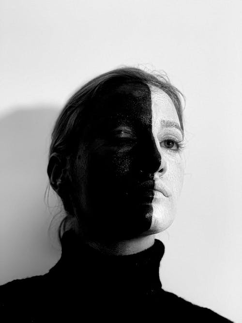 Black and white from below of weird female with greasepaint on face looking away while standing on white background with closed eye