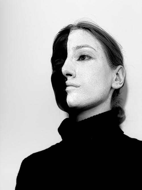 Black and white from below of spooky female with paints on face wearing turtleneck looking away while standing against white background