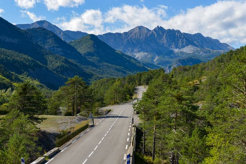 Concrete Road Between Green Trees and Mountains