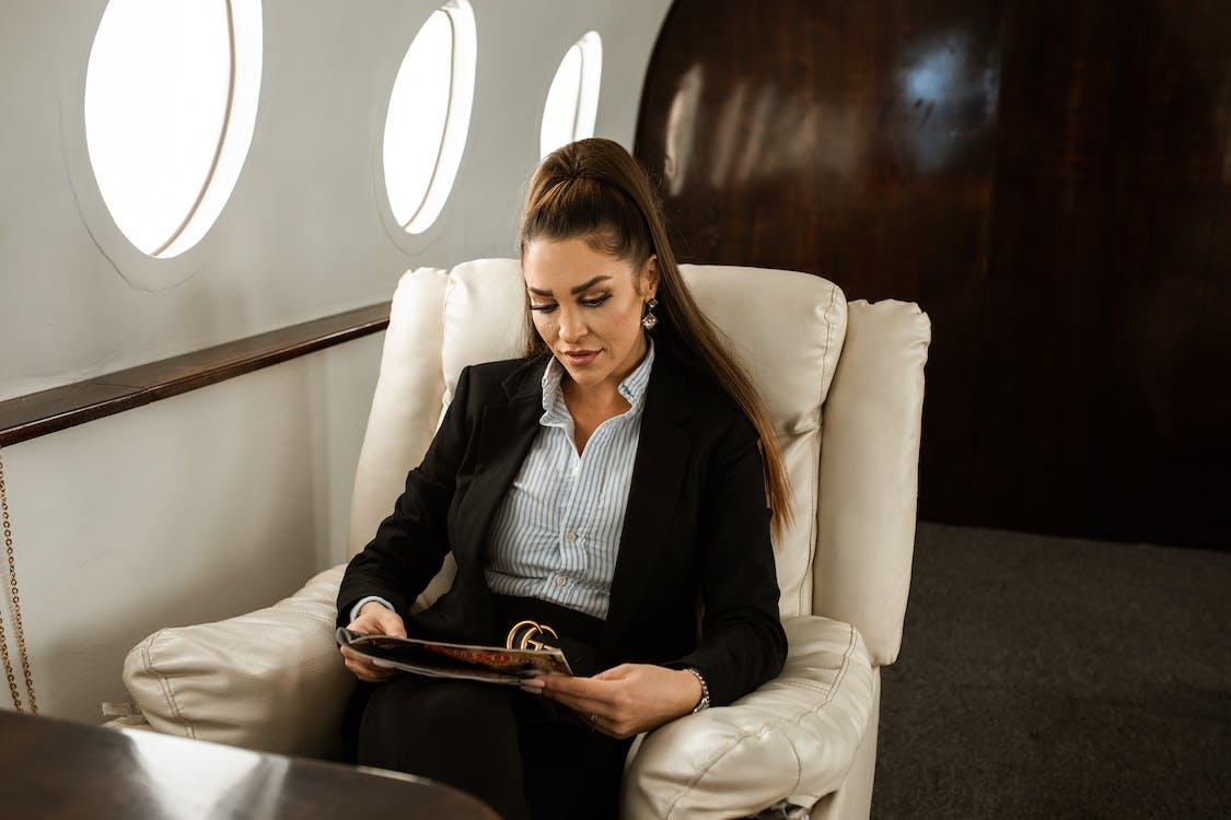 Woman in Black Blazer Sitting on White Sofa