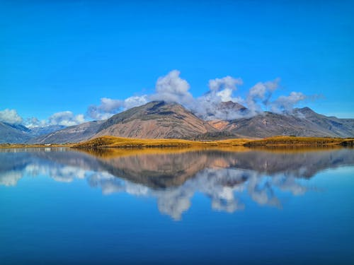 High mountains under clouds reflecting in calm lake