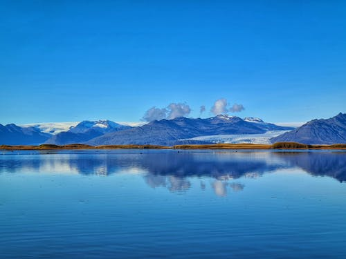 Snowy mountains reflected in rippling water of lake