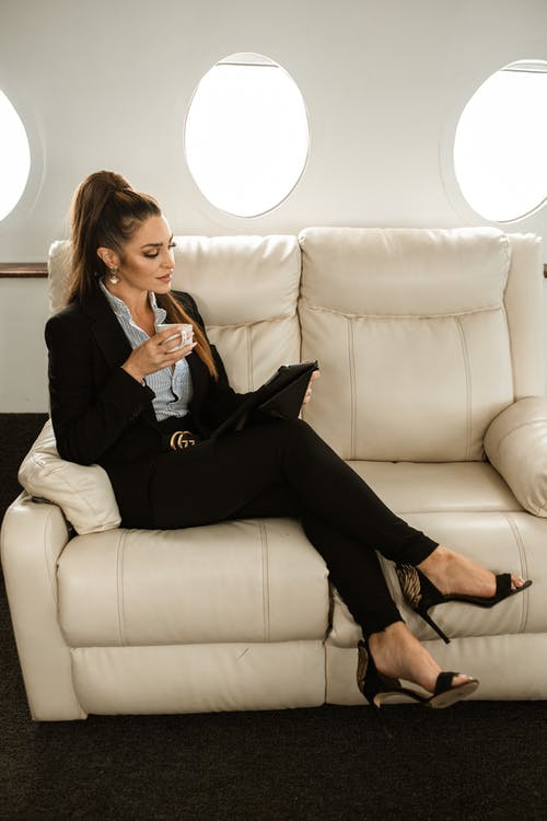 Woman in Black Blazer and Black Pants Sitting on White Couch