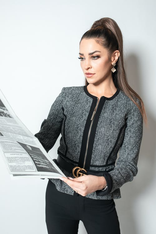 Woman in Gray and Black Long Sleeve Shirt Holding White Printer Paper