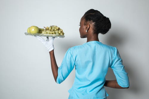Woman in Teal Crew Neck T-shirt Holding Green Apple Fruit