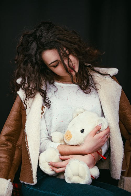 Woman in Brown Coat Holding White Bear Plush Toy
