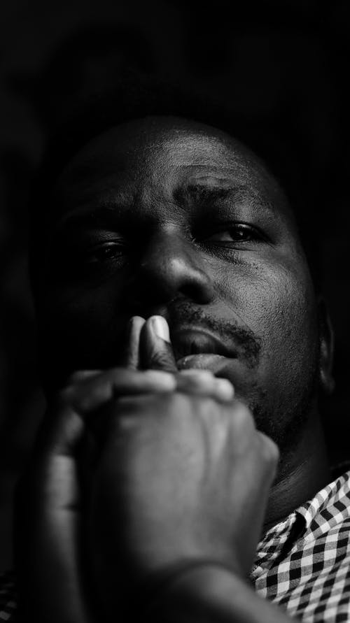 Sad black man touching lips and thinking in darkness