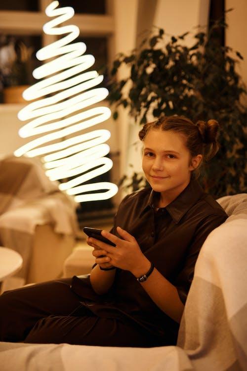 Adolescente Sonriente Con Smartphone En El Sofá Cerca De La Lámpara Brillante