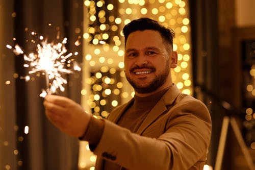 Man in Brown Coat Smiling While Holding a Burning Sparkler