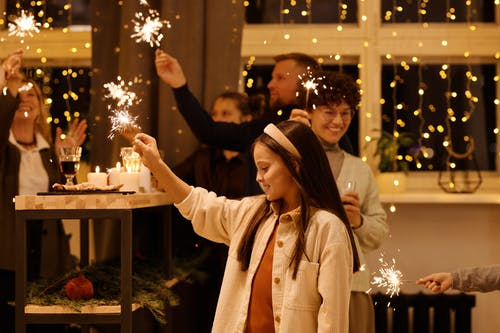 Family Celebrating Christmas While Holding Burning Sparklers