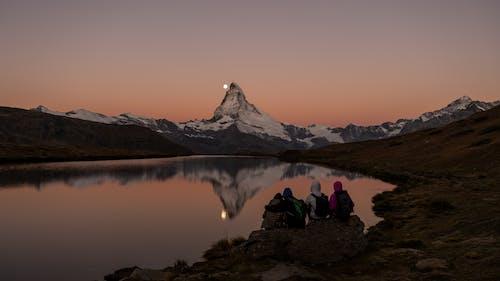 People Sitting on Rock Near Lake