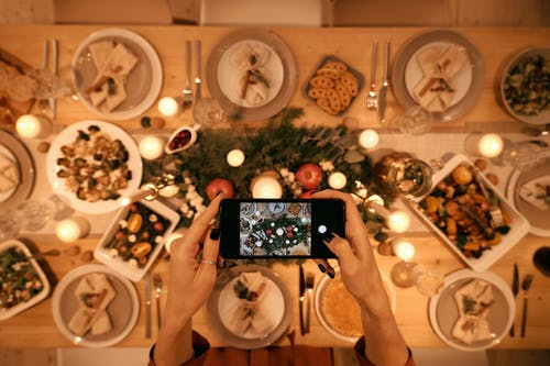 Top View of a Person Taking Picture of Christmas Dinner