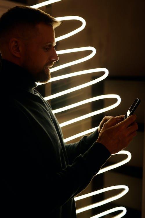 Homme En Chemise à Manches Longues Noire Tenant Un Smartphone