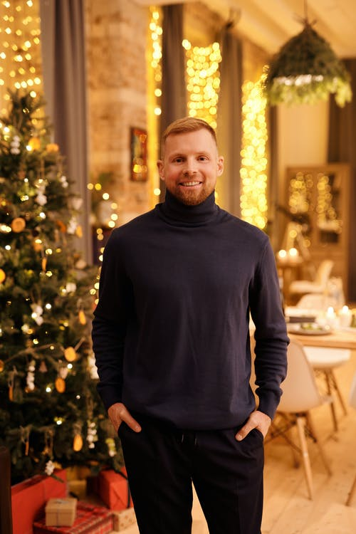 Man in Black Turtleneck Long Sleeve Shirt Standing Near Christmas Tree