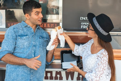 Cheerful grimacing couple in casual clothes clinking sandwiches while standing near food truck and looking at each other