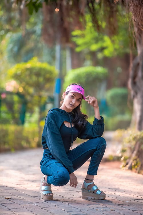 Woman in Pink Hat and Blue Denim Jeans Sitting on Concrete Pavement