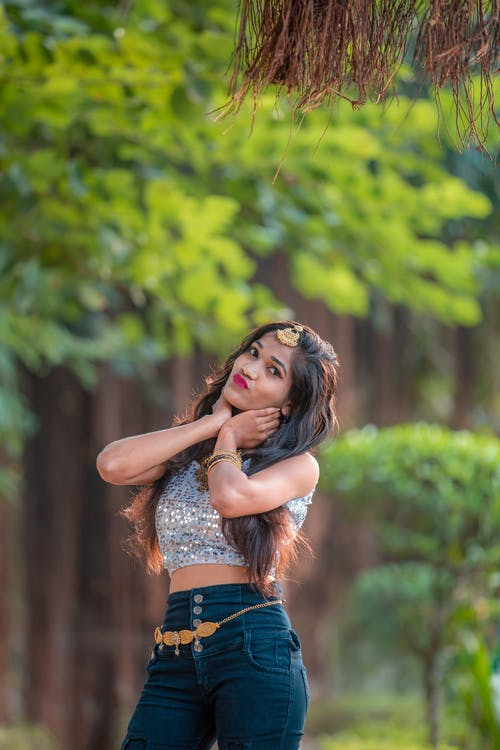 Woman in White Sequins Crop Top and Blue Denim Shorts Standing Near Green Tree