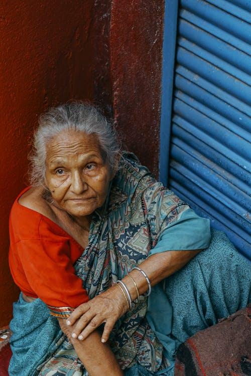 Wanita Etnis Lanjut Usia Duduk Di Dekat Dinding