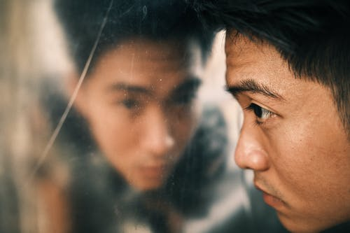 Side view of crop young serious Asian man looking in dirty mirror in daytime