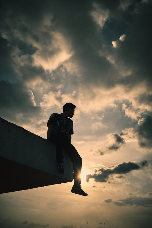 From below of anonymous young male sitting on edge of roof and looking away against cloudy sunset sky