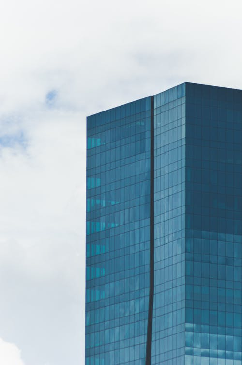 Contemporary tall glass skyscraper under blue sky in white clouds in urban city