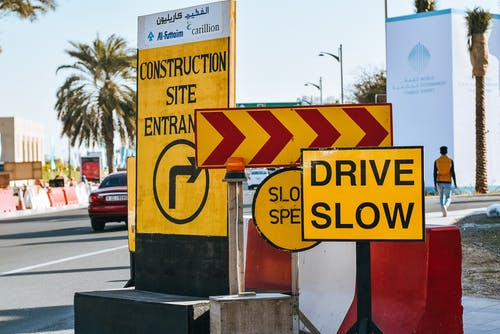 Contemporary city road on sunny day with various traffic signs warning about driving slow because of construction site entrance
