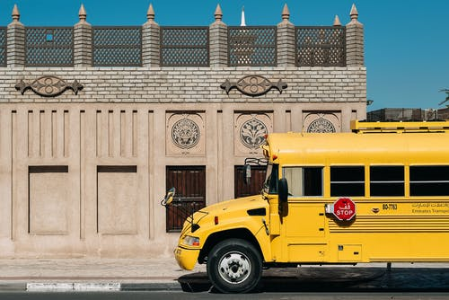 Yellow school bus with red stop warning sign parked on empty street with authentic brick building on bright day