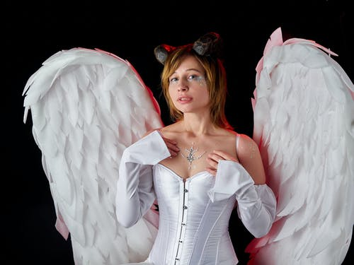 Extravagant female wearing corset with decorative rhinestones on chest and face with feather wings on back for Halloween