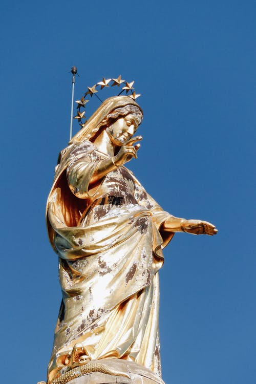 Low angle of famous golden sculpture of Virgin Mary in crown of stars placed on pillar against blue sky outside