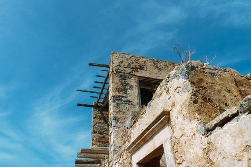 From below of damaged stone building with window holes and timber on roof against blue sky in countryside in sunlight
