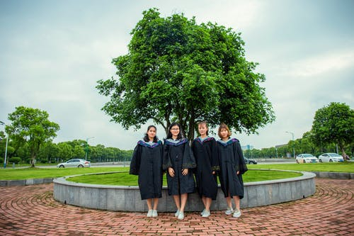 People in Black Academic Dress Standing on Brown Brick Pathway