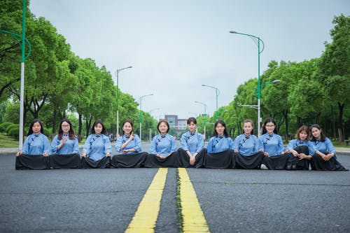 Group of People Sitting on Gray Asphalt Road