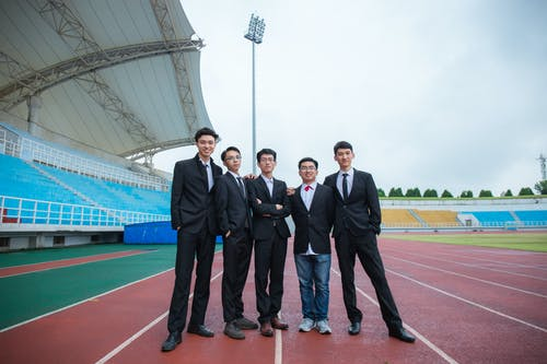 3 Men in Black Suit Standing on Track Field