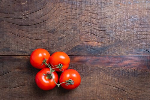 Red Tomatoes on Brown Wooden Table