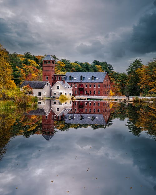 Peaceful lake reflecting aged houses and lush autumn trees under overcast sky